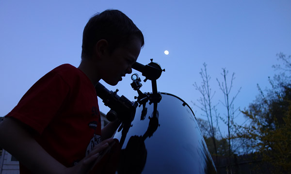 A boy and his Dob viewing the Moon.